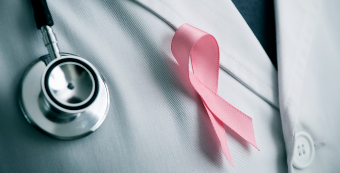 closeup of white doctor's coat with stethoscope and pink breast cancer awareness ribbon