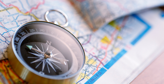 A compass sits on top of a road map. The image is captured using a very shallow depth of field.