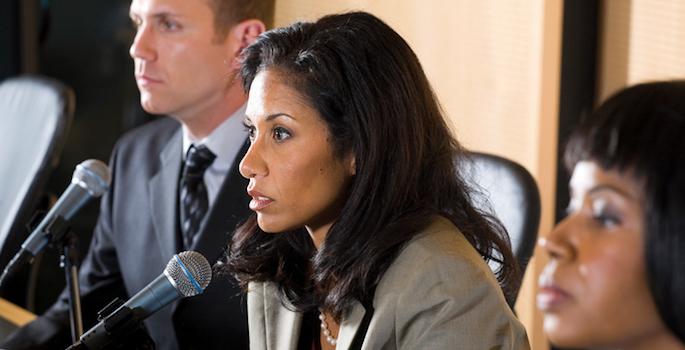 Woman on legislative committee speaking into microphone flanked by one female legislator and one male legislator