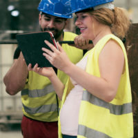 Pregnant woman and male coworker wearing hard hats and safety vests looking at ipad in factory
