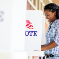 A young black woman voting on election day