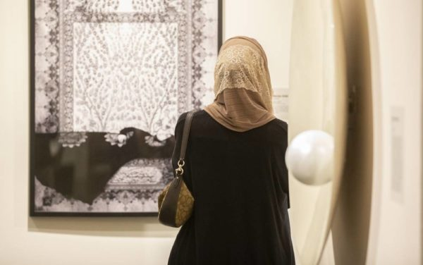 An attendee of the 'I AM' opening reception views a piece of art in the Vanderbilt Fine Arts Gallery.