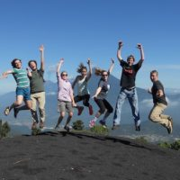 students jumping in the air on top of volcano