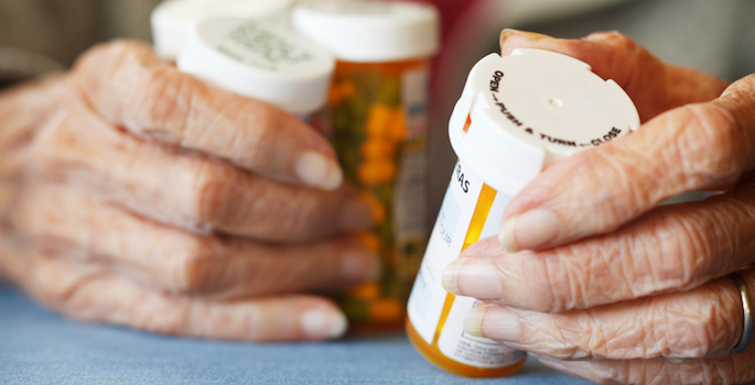 Close up of Senior citizen female holding bottles of prescription medicine.