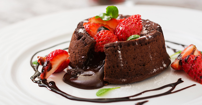 Fancy molten chocolate cake with raspberries and chocolate swirls on white plate