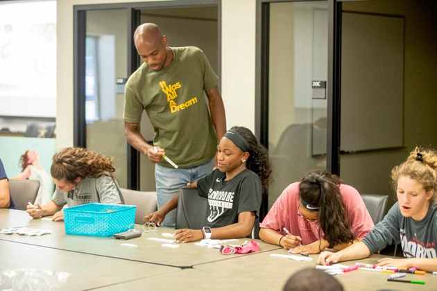 During a workshop organized by the Curb Center, Nashville artist Omari Booker mentors first-year student-athletes for a collaborative art project. (John Russell/Vanderbilt)