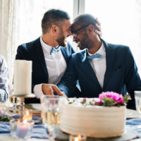 Interracial gay couple celebrates wedding with loved ones