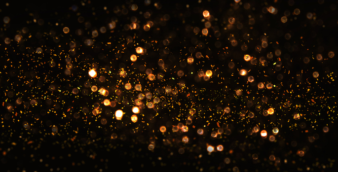 Gold glitter scattered on black background