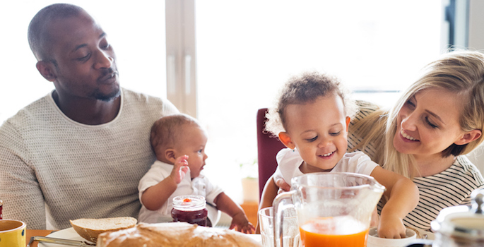 African American dad and Caucasian mom enjoying breakfast with their super adorable kids