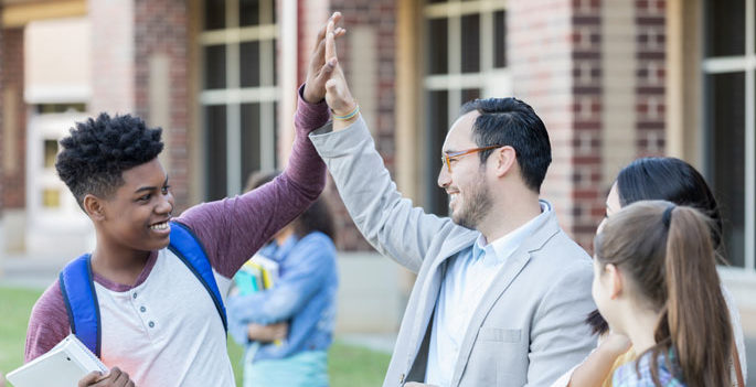 african american teenage high-fives caucasian or hispanic principal outside a school building