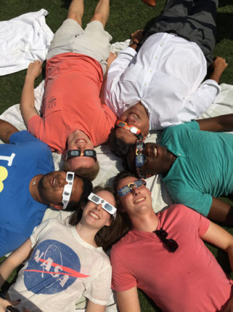 Alexandra Doten (bottom left) and friends watch the total solar eclipse on campus with Chancellor Nicholas S. Zeppos (top right) on August 21, 2017.