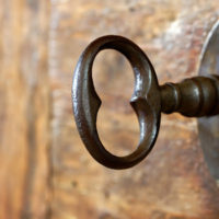 Closeup of an old keyhole with key on a wooden antique door