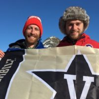 dan and andrew holding a vanderbilt flag in the antarctic snow