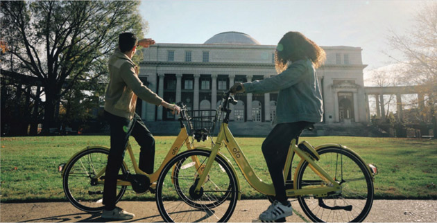 Two students sitting on bikes on campus