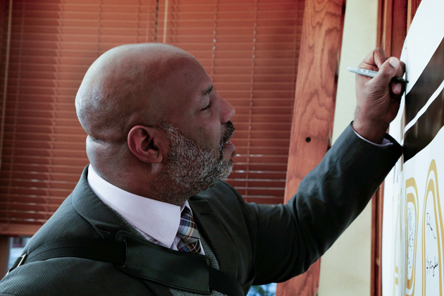 "Jelani Cobb signs ""The Zeppos Report"" poster before his Jan. 17 lecture. (Vanderbilt University)"