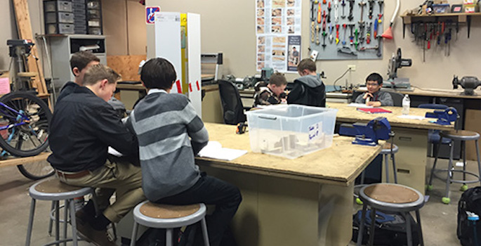 Young boys get hands-on engineering education at a work table in at STEM school