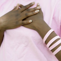 African American woman in pink crossing her hands over her breast