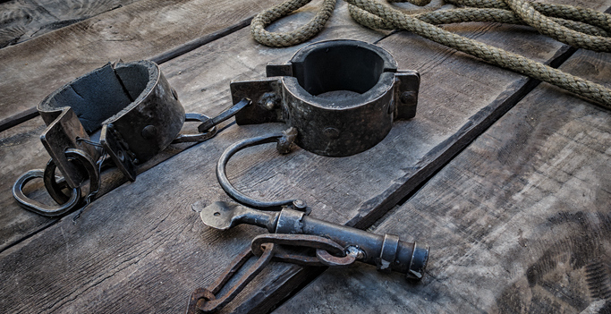 close-up of iron shackles lying on the deck of a ship