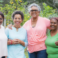 four african american women posing for a photo outside. some are overweight.