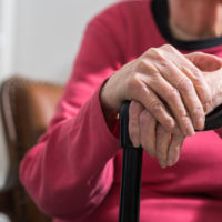 Elderly caucasian woman with her hands on a cane