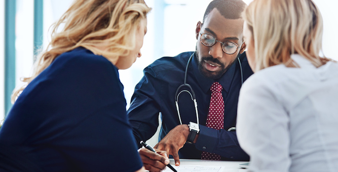 african american doctor consulting with two women in office