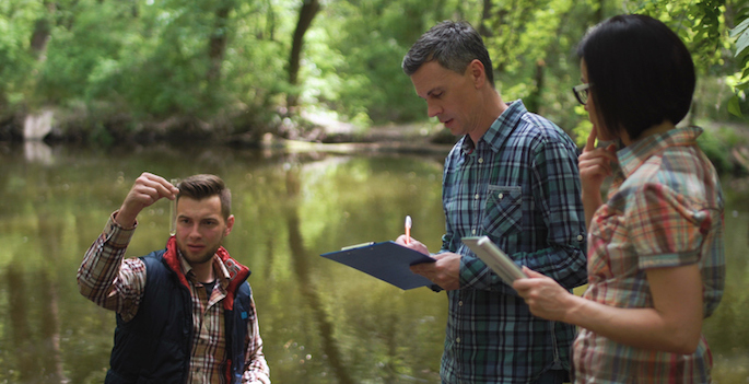 A professor and two students testing water quality in a creek