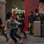 shoppers running from behind barricades into store on black friday