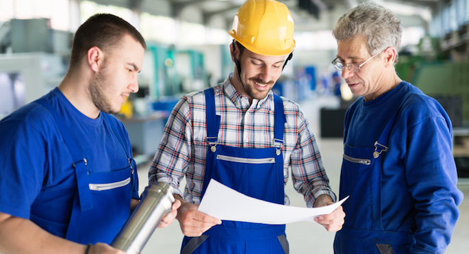factory workers looking at blueprints
