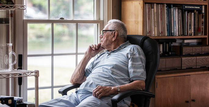 elderly man lost in thought and looking out window in home office
