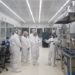 five adults in white hazmat suits touring cleanroom facility