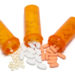 Three overturned prescription bottles spilling out three kinds of pills, symbolizing combination therapy