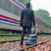 traveler dragging suitcase along train tracks as a missed train rushes past