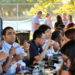 Postdocs and some children enjoying picnic meals at a long picnic table in the park