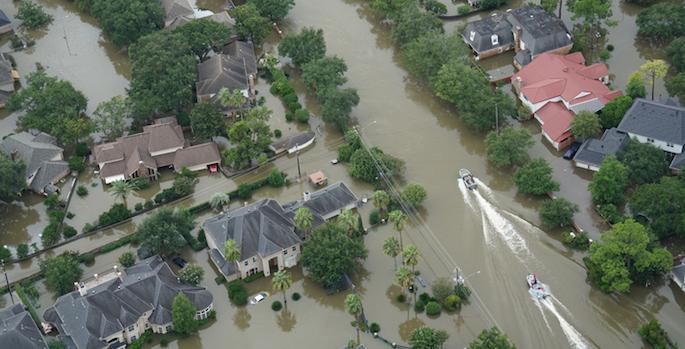 overhead photo of boats floating through flooded neighborhood