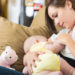 Young mom breastfeeding infant daughter at home