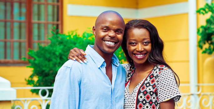 Happy african couple embracing in front of their new house.