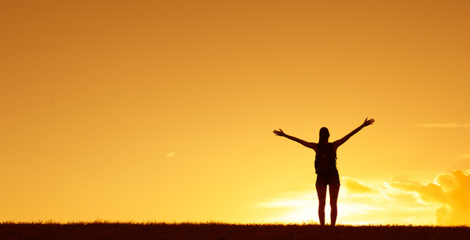 Silhouette of woman with arms raised joyfully against the sunset