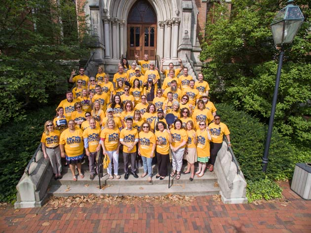 Members of the Division of Communications and the Office of the Chancellor wear their #UnitedInGold T-shirts on the steps of Kirkland Hall. (Susan Urmy/Vanderbilt)