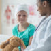young bald girl in hat visiting her oncologist, an african american female doctor