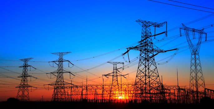 The silhouette of electricity transmission pylons at sunset
