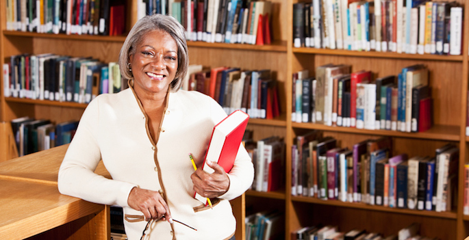 Mature African American woman in suit standing in school library