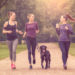 Four slender young white women jogging in the park