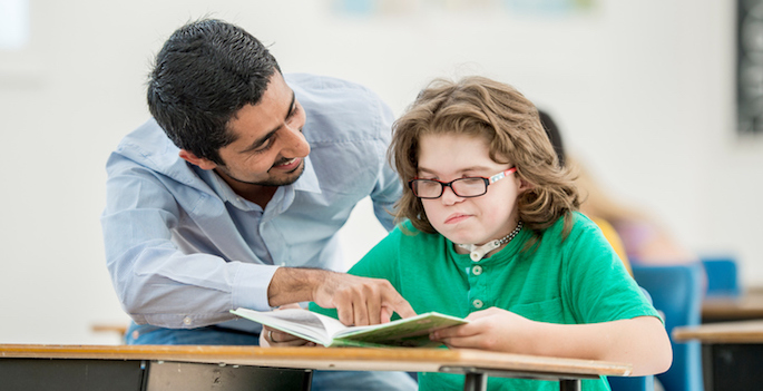 teacher assisting frustrated disabled child with reading