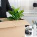man carrying box full of desk items away from desk