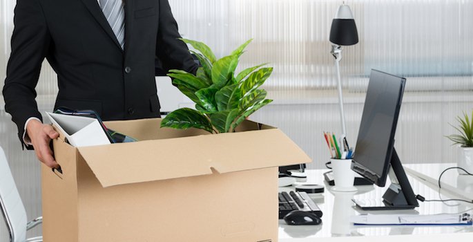 man carrying box full of desk items away from desk