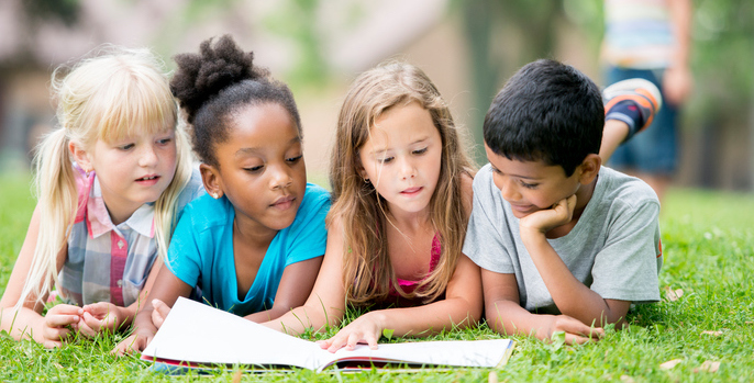 A multi-ethnic group of elementary aged children are reading a book in the park.