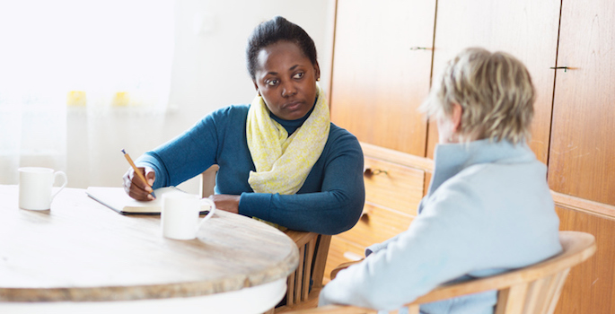 social worker listening to a client, sitting at table and taking notes