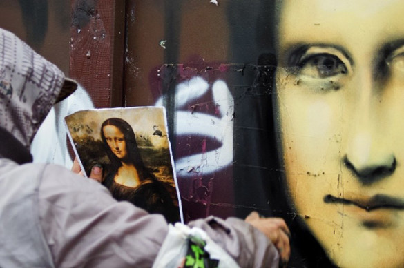 Vilnius, Lithuania - Sept. 6, 2011: Graffiti artist drawing Mona Lisa on a wall while looking into a picture of actual painting. He is painting it at a Nescafe Street Art event were graffiti artists made legal graffiti painting at a skate park. (iStockphoto)