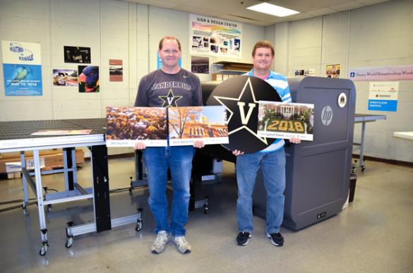 Prepress technician Roger Sauls (left) and prepress supervisor Sam Daugherty display products created using Vanderbilt University Printing Services' new flatbed UV printer.
