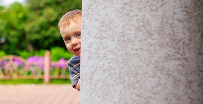 child hiding behind a corner